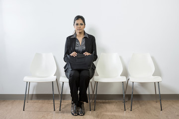 Nervous looking Indian business woman waiting.