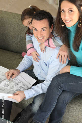Young family relaxing on sofa with newspaper