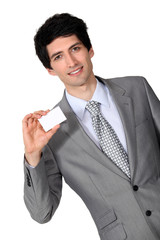 portrait of handsome businessman holding business card