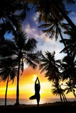 Yoga tree pose around palm trees