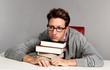Erschöpfter junger Mann liegt auf seinen Büchern