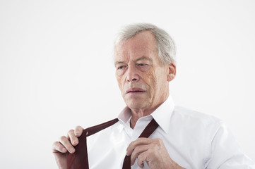Elderly man putting on his tie