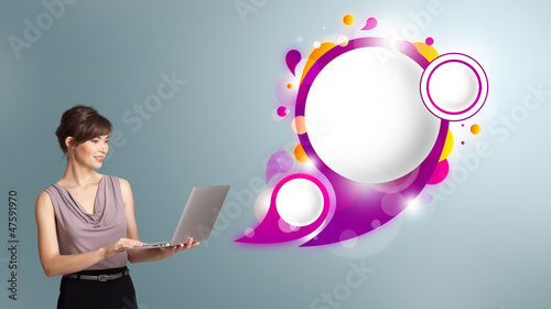 attractive woman holding a laptop and presenting abstract speech