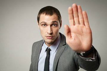 a young businessman showing stop gesture