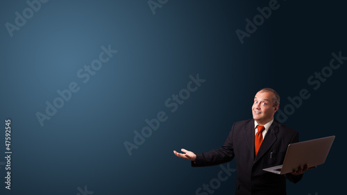 businessman holding a laptop and presenting copy space