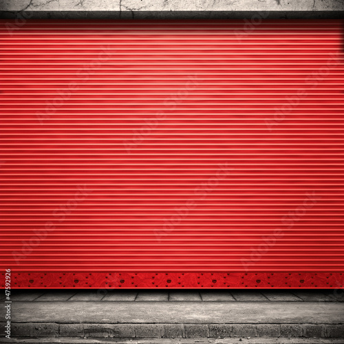 Painted corrugated metal door with conrete wall and ground.