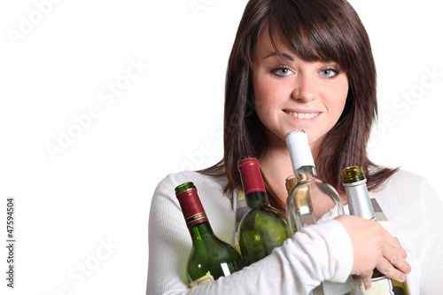 young woman holding empty wine bottles