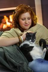 Smiling teenage girl fondling cat at home