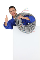 Electrician with long cable giving the thumbs-up