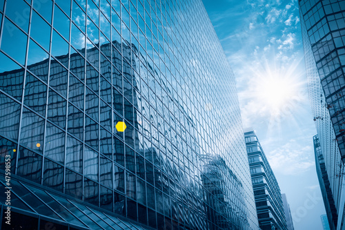 modern glass building under the blue sky