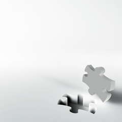 gray puzzle in the corner of white surface
