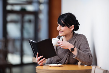 Young woman sitting in the restaurant with digital tablet