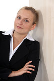 Blond businesswoman casually leaning against wall