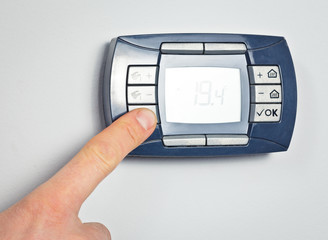 Finger pushing thermostat control button