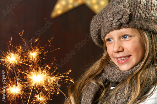 Cute girl looking at festive fire sparks.
