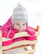 Portrait of cute little girl sitting in sled