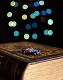Old book and miniature car on bokeh lights background