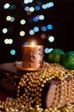 Burning candle and seasonal decorations on bokeh lights