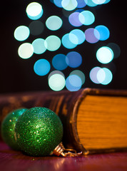 Old book and seasonal decorations on bokeh lights background