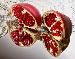 Two slices of ruby pomegranate in water jet