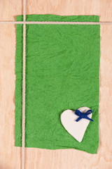 card from crumpled paper, stone heart and rope on wooden