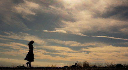 Silhouette of young woman walking