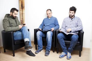 Drei Mann warten gelangweilt beim Arzt