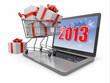 Happy new year 2013. Laptop and gifts on shopping cart.