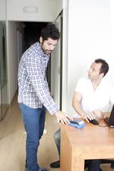 Mann zahlt für medizinische Behandlung mit Kreditkarte