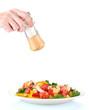 Hand adding salt using  salt shaker isolated on white
