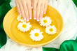 woman hands with wooden bowl of water with flowers