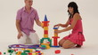 Two adults building a toy tower