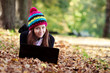 Beautiful teenage girl working on laptop in park during autumn