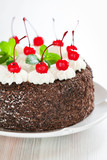 Chocolate cake with whipped cream and glazed cherries