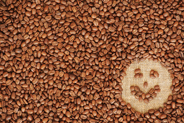 face coffee frame made of coffee beans on burlap texture