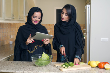 Two Young Arabian Women Checking Recipe on a mobile pad