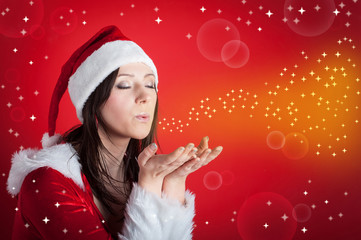 Christmas woman blowing portrait on red background.