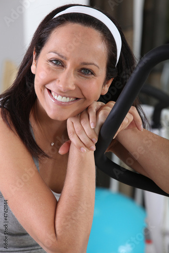 dark-haired woman posing in gym