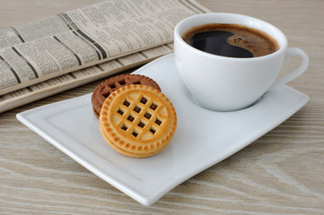 A cup of coffee and biscuits and a newspaper