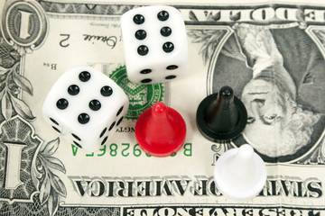 Board game figures and two dice against a banknote