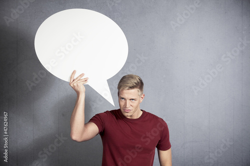 Angry man holding white empty speech ballon.