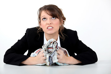 angry businesswoman crushing a newspaper