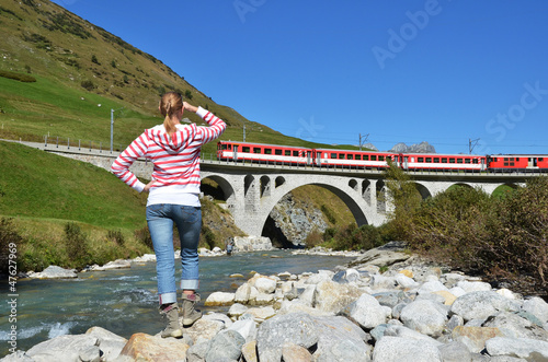 Girl looking at the train, which crosses a bridge. Switzerland