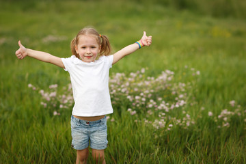 Happy little girl showing thumb us signs outdoors