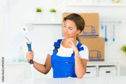 heimwerkerin schaut nachdenklich auf die farbrolle