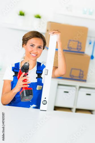 heimwerkerin mit akkuschrauber und wasserwaage