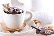 Cup of hot chocolate with pieces of chocolate and almond on ligh