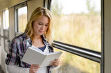 Woman reading a book by train window