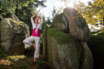 Woman Yoga standing between Rocks
