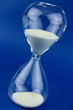 Hourglass on blue background. Close up image.